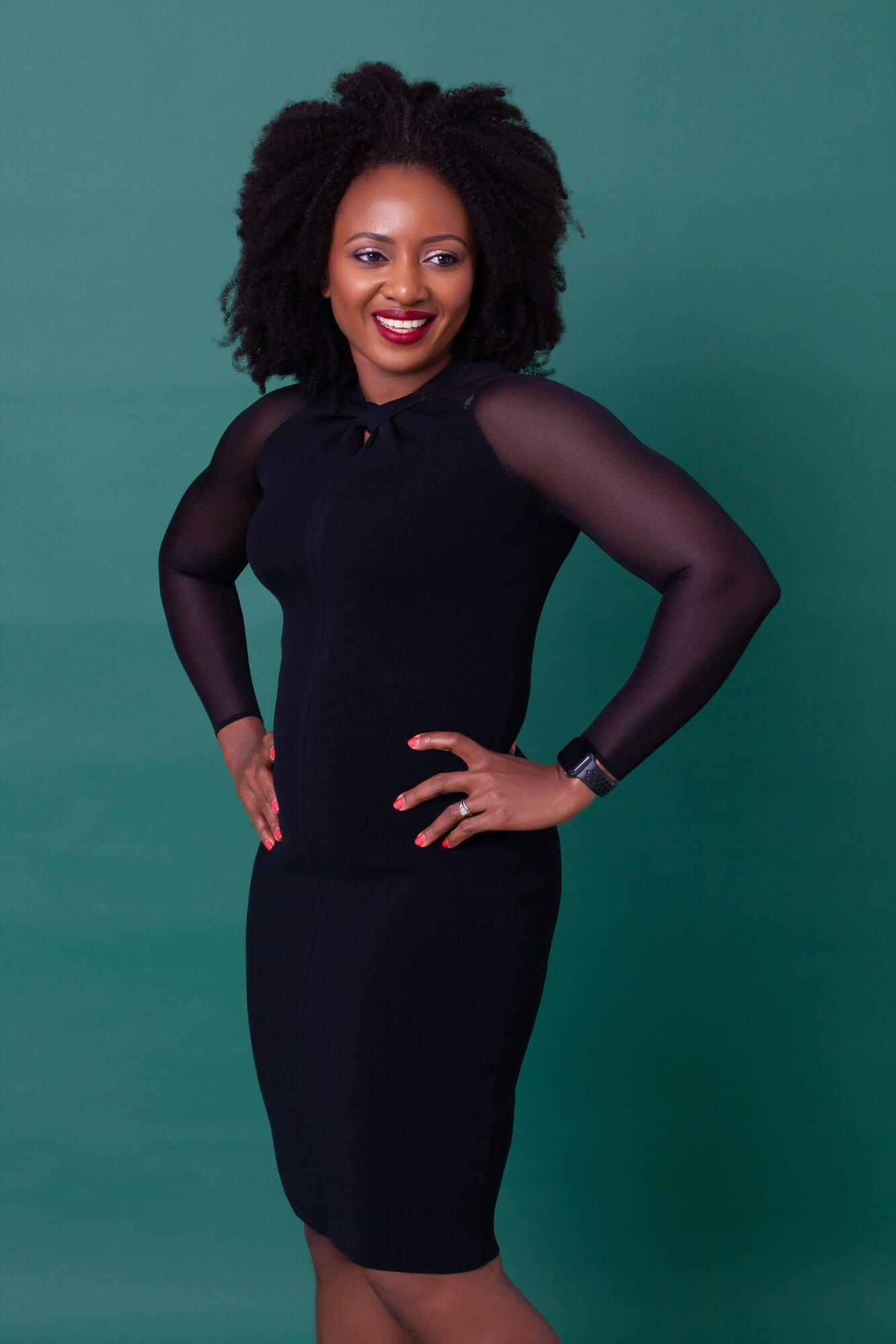 April Laugh in a back dress stood in front of a dark green background.