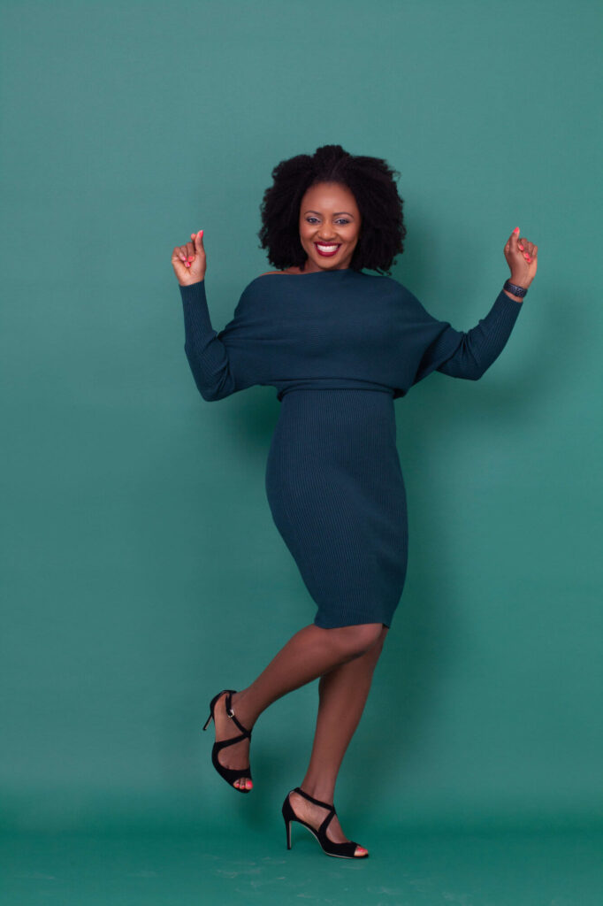 April Laugh in a dark green dress, in front of a dark green backdrop.